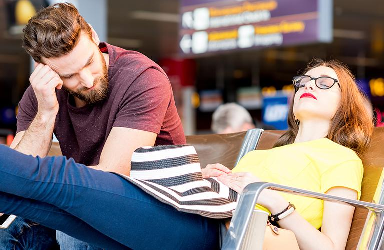 Un couple attend à l'aéroport son vol retardé ou annulé