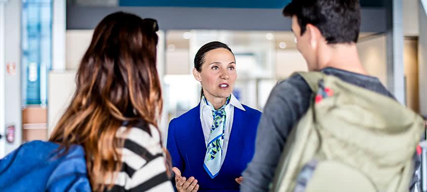 Flughafenpersonal diskutiert mit Passagieren
