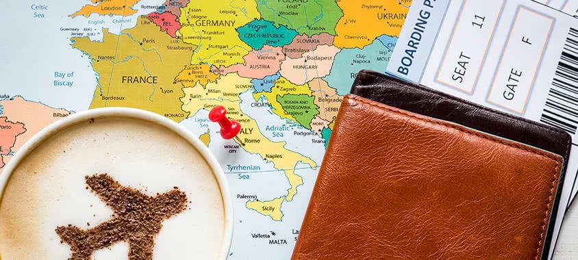 Reiseunterlagen auf einer Landkarte mit Kaffee